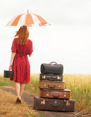 Redhead girl with suitcases at outdoor — Stock Photo