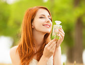 Redhead girl with perfume at outdoor — Stock Photo