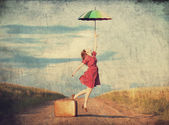 Redhead girl with umbrella and suitcase at outdoor — Stock Photo