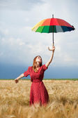 Redhead girl with umbrella at field — Stock Photo