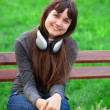 Brunette girl with headphones sitting at the bench in the park. — Stock Photo