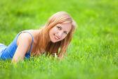 блондинка lyinig в зеленой траве — Стоковое фото