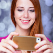 Redhead girl using mobile phone. — Stock Photo