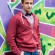 Style teen boy near graffiti background. — Stock Photo