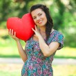 Foto Stock: Young beautiful pregnant womwith toy heart in park