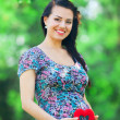 Young beautiful pregnant woman with toy heart in the park — Stock Photo