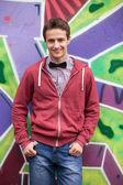 Style teen boy near graffiti background. — Stock Photo