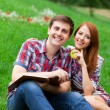Young students sitting on green grass with note book. — Stock Photo #28486703