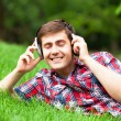 Handsome young man with headphones at green grass — Stock Photo #28487085