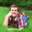 Handsome young man with headphones at green grass — Stock Photo #28488135