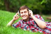 Красивый молодой человек с наушниками на зеленой траве — Стоковое фото