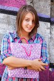 Style teen girl standing near graffiti wall. — Stockfoto