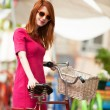 Redhead girl with bike at outdoor, city. — Stock Photo #28860393