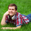 Handsome young man with headphones at green grass — Stock Photo
