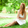 Redhead women lying at green grass — Stock Photo