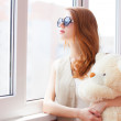Sad grunge girl near window with toy bear — Stock Photo