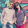 Style teen couple near graffiti background. — Stock Photo