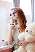 Sad grunge girl near window with toy bear — Stock Photo