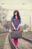 Young fashion girl with suitcase at railways. — Stock Photo