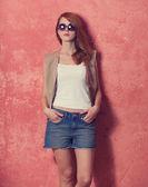 Piękny rudy dziewczynka ilustracja blisko ściany. — Zdjęcie stockowe