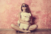 Sad grunge girl near wall with teddy bear — Stock Photo