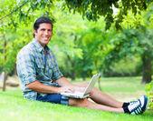 Student met laptop op groen gras — Stockfoto