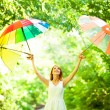 Redhead girl with three umbrellas at outdoor — Stock Photo #29280841
