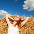 Redhead girl lying down on hay — Stock Photo