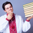 Man in embroidery shirt with books. — Stock Photo