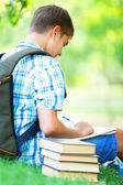 Teen boy with books and notebook at outdoor. — Stock Photo