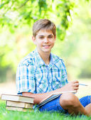 Teen boy with books and notebook in the park. — Stock Photo