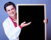 Handsome man in national embroidery with blackboard. — Stock Photo