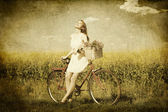 Girl on a bike in the countryside — Stock fotografie