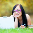 Teen girl with laptop in the park. — Stock Photo
