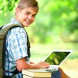 Teen boy with books and laptop in the park. — Stock Photo