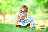 Teen boy with books in the park. — Photo