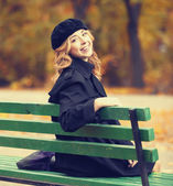Style redhead girl sitting at bench in autumn park. — Stock Photo