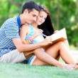 Young students sitting on green grass with note book. — Foto Stock