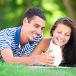 Young students sitting on green grass with note book. — Stock Photo