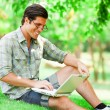 Stock Photo: Student with laptop at green grass