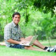 Student with laptop at green grass — Stock Photo #30507415