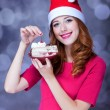 Redhead girl in christmas hat with cake — Stock Photo #30507517