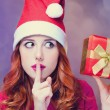 Redhead girl in christmas hat with gift. — Stockfoto