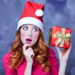 Redhead girl in christmas hat with gift. — Stock Photo