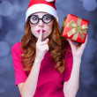 Redhead girl in christmas hat with gift. — Stock Photo #30507689