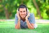 Jovem bonito com fones de ouvido na grama verde — Foto Stock