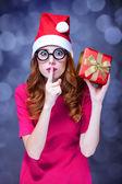 Pelirroja en sombrero de la navidad con regalo. — Foto de Stock