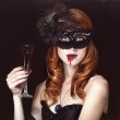 Redhead vampire woman in mask with glass of blood. — Stock Photo #30574391