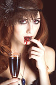 Redhead vampire woman with glass of blood. Photo in vintage styl — Zdjęcie stockowe