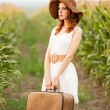 Redhead girl with suitcase — Stock Photo